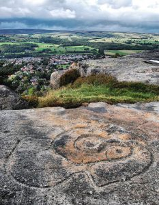 Evidence of early civilisations can be found on Ilkley Moor. These carvings date back to The Bronze Age. Picture credit: TJ Blackwell wikipedia creative commons.