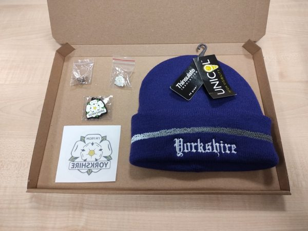 purple beanie inside a cardboard box with an I'm From Yorkshire window sticker, keyring, badge and a Yorkshire and England flag badge