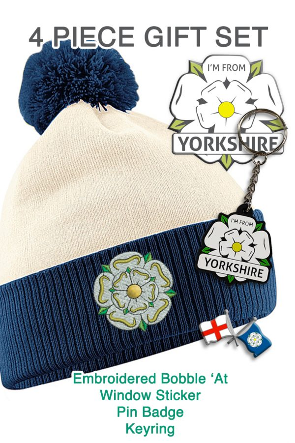 promotional image with an off white and navy bobble hat, an I'm From Yorkshire sticker, keyring and badge
