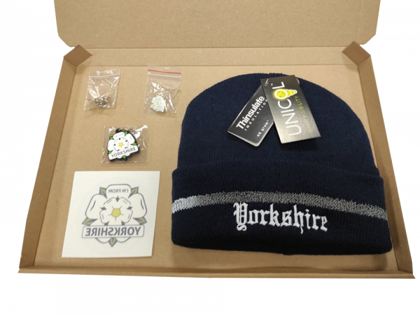 navy yorkshire embroidered beanie, yorkshire window sticker, keyring, two badges inside gift box with transparent background