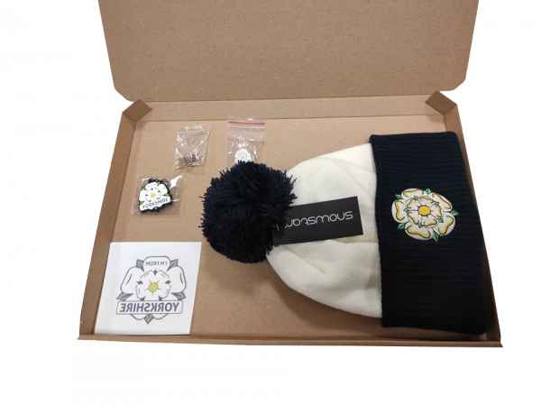 off white and navy yorkshire rose embroidered bobble hat, yorkshire window sticker, keyring, two badges inside gift box with transparent background